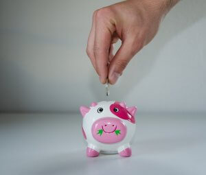 Man saving money in a pink piggy bank